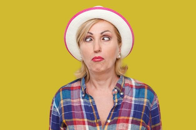 흰 모자를 쓰고 눈을 교차하고 재미있는 얼굴 표정을 하고 있는 캐주얼 스타일의 미친 십자형 세련된 성숙한 여성의 클로우즈업 초상화. 노란색 배경에 격리된 실내 스튜디오 샷입니다.
