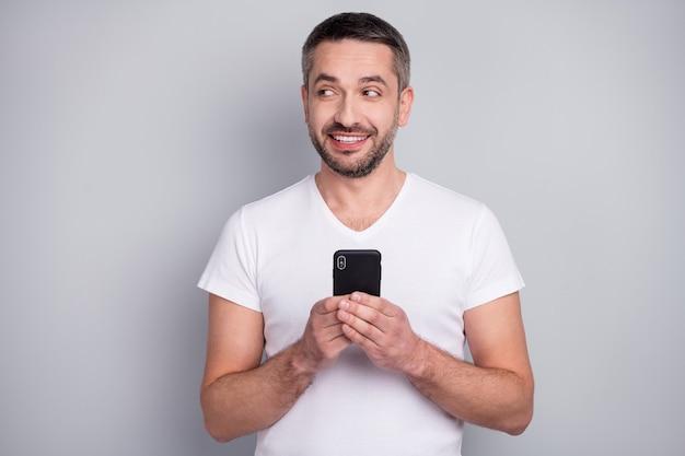 Портрет крупным планом творческого любопытного веселого парня, использующего телефон, выглядит пустым пространством