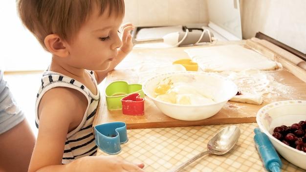 부엌에 서서 반죽을 요리하는 귀여운 3세 소년의 클로즈업 초상화. 베이킹과 아침 식사를 만드는 아이