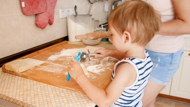 부엌에 서서 반죽을 요리하는 귀여운 3 년 유아 소년의 근접 촬영 초상화