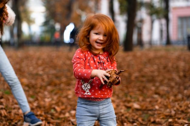 カメラを見て幸せなライフスタイルの子供時代のコンセプトの外に秋の秋の公園に立って、乾燥した葉で遊んでかわいい愛らしい笑顔の小さな赤い髪の白人の女の子子供のクローズアップの肖像画