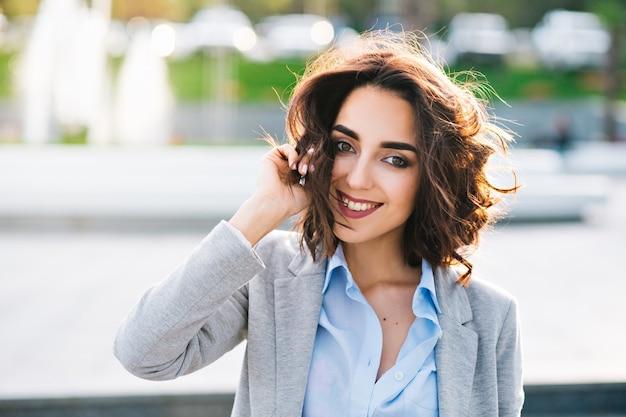 市でポーズをとって短い髪のかわいいブルネットの少女のポートレート、クローズアップ。彼女は青いシャツ、灰色のジャケットを着ています。彼女は髪に触れてカメラに微笑んでいます。