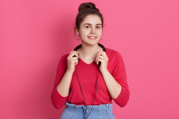 Портрет крупного плана милой очаровательной предназначенной для подростков девушки нося розовую блузку