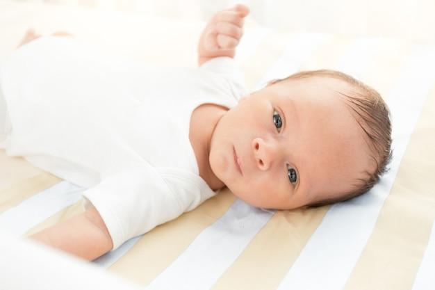 Портрет крупным планом милый новорожденный ребенок, лежа в постели