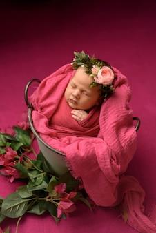 Портрет крупного плана милого спать новорожденного младенца обернутого в фиолетовом мягком одеяле, нося стильный головной цветок, концепция моды младенца