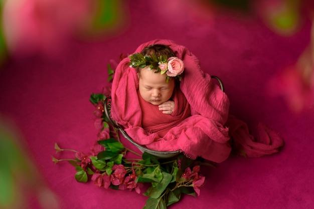 Портрет крупного плана милой спать newborn девушки обернутой в фиолетовом мягком одеяле, нося стильном головном цветке, концепции моды младенца
