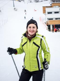 Портрет крупным планом милой улыбающейся лыжницы на спуске горнолыжного склона