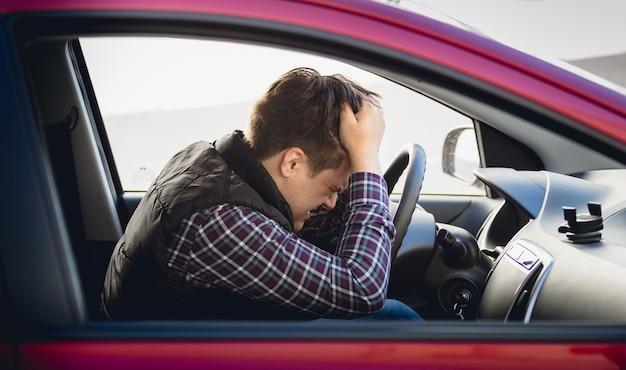 車を運転して落ち込んでいる男のクローズアップの肖像画