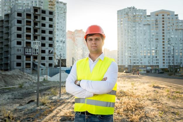 Крупным планом портрет инженера в каске позирует против строящегося здания
