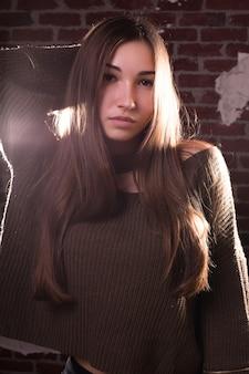 세련된 갈색 머리 여성의 클로우즈업 초상화는 대형 스웨터를 입고 벽돌 벽 배경에 포즈를 취합니다.