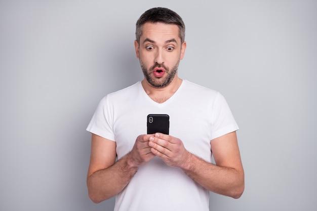 Портрет крупным планом забавного парня, возбужденное лицо с открытым ртом, читать телефонный интернет-пост