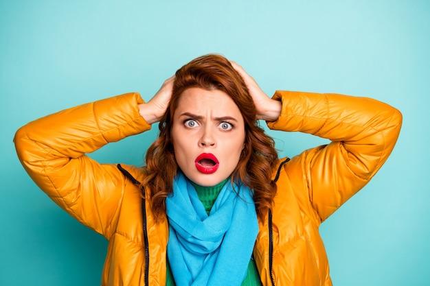 頭の開いた口の上の面白い女性の腕のクローズアップの肖像画は、目の壮大な失敗が黄色のオーバーコート青いスカーフ緑のタートルネックを着用するとは思わない。