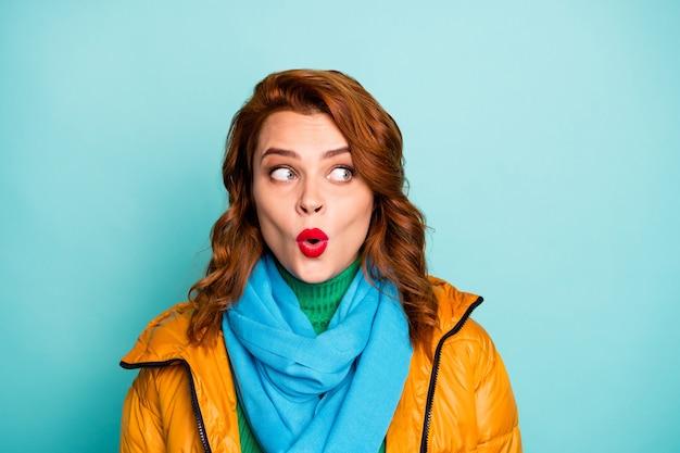 재미있는 레이디 오픈 입의 클로 우즈 업 초상화 들어 믿을 수없는 뉴스 구매자 모습 측면 빈 공간 착용 노란색 외투 파란색 스카프 녹색 터틀넥.