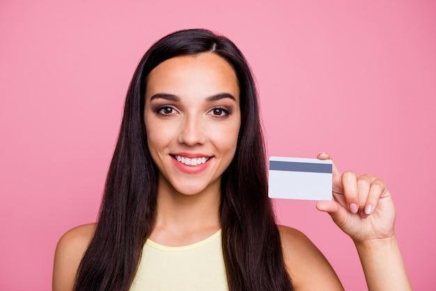 Портрет крупным планом девушки, держащей кредитную карту, изолированную над розовой стеной