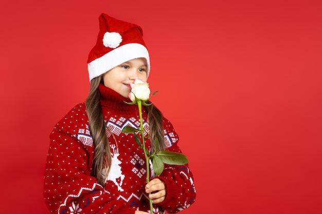 Крупным планом портрет девушки в красном вязаном рождественском свитере с оленями и шляпой санта-клауса нюхает ...