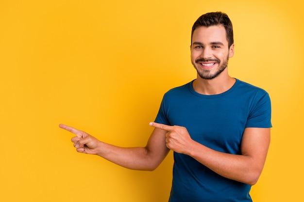 Портрет крупным планом радостного веселого парня, указывая двумя указательными пальцами