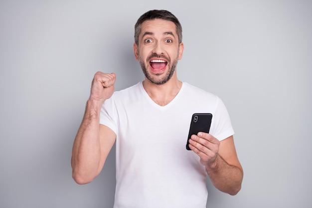 Портрет крупным планом радостного, взволнованного веселого парня, использующего телефон, празднует победный крик