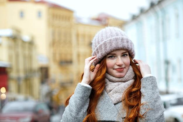 通りでポーズをとってニットの暖かい帽子とスカーフを身に着けているゴージャスな赤い髪の女性のクローズアップの肖像画。テキスト用のスペース