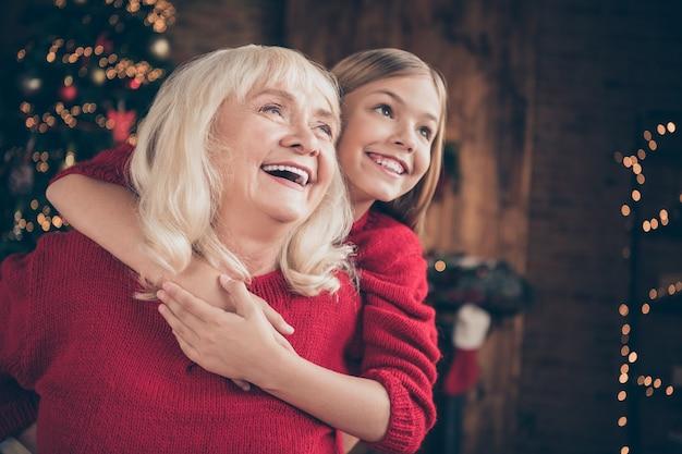 おばあちゃんの孫の抱擁のクローズアップの肖像画は、装飾されたロフトのインテリアハウスで休暇をお楽しみください