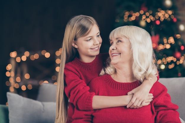Портрет крупным планом внука бабушки сидит на диване и обнимается в украшенном доме