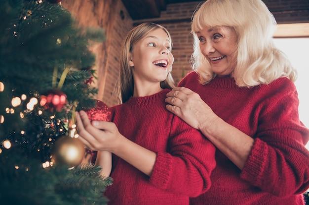 装飾されたインテリアハウスでモミの楽しみにおもちゃをぶら下げおばあちゃんプレティーン孫のクローズアップの肖像画