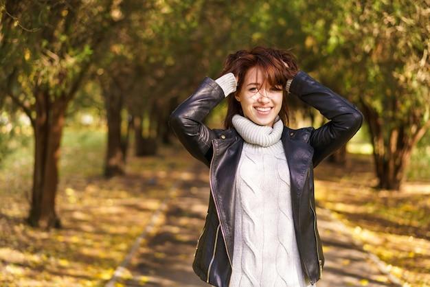 검은 옷을 입고 공원에서 산책 하는 매력적인 세련 된 여자 얽히고 설킨 머리의 손의 근접 촬영 초상화...