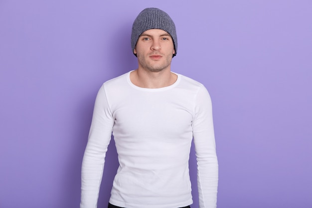 잘 생긴 마그네틱 남자의 라일락에 고립, 회색 모자와 흰색 셔츠를 입고, 강한 맞는 유지의 근접 촬영 초상화. 추운 시간 개념입니다.