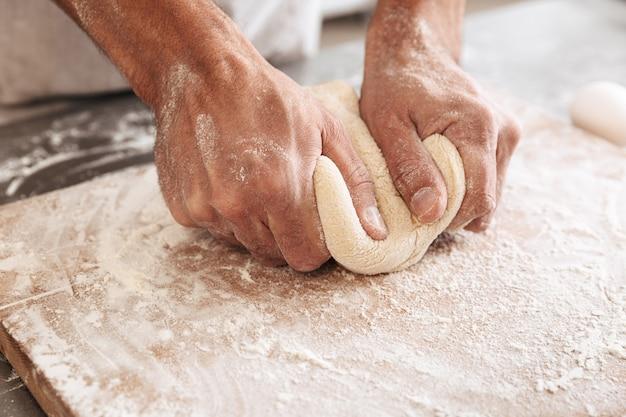 빵집이나 부엌에서 테이블에 빵 반죽을 만드는 잘 생긴 남성 손의 근접 촬영 초상화