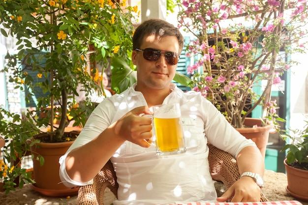 더운 날에 레스토랑에서 맥주를 마시는 잘 생긴 남자의 근접 촬영 초상화
