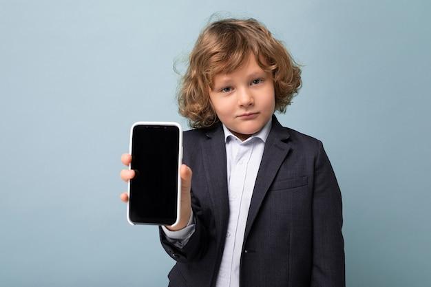 Портрет крупным планом красивого позитивного мальчика с вьющимися волосами в костюме, держащего телефон