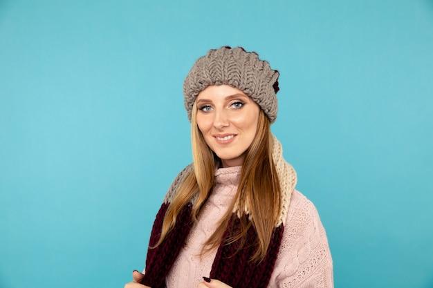 파란색 배경 위에 절연 겨울 모자 scaf에 잘 생긴 웃는 여자의 근접 촬영 초상화.