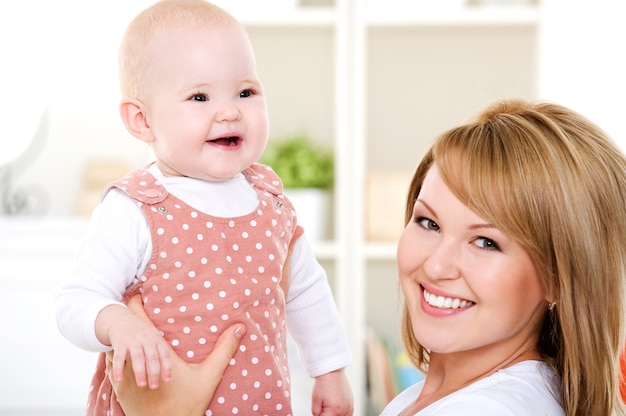 Крупным планом портрет счастливой матери с новорожденным ребенком - в помещении