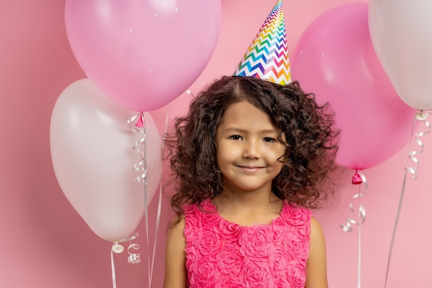 Портрет крупного плана счастливого положительного маленького ребенка нося праздничную одежду, шляпу дня рождения, стоя среди воздушных шаров. дети, праздник и концепция празднования.