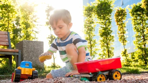 Портрет крупного плана счастливого улыбающегося 3-летнего мальчика, копающего песок на детской площадке с игрушечным пластиковым грузовиком или экскаватором. ребенок играет и веселится в парке летом