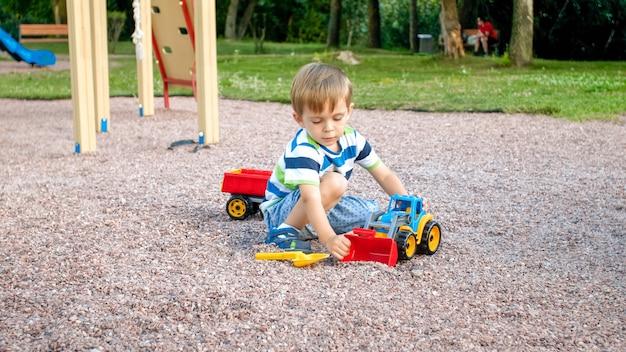장난감 플라스틱 트럭이나 굴삭기와 놀이터에서 모래를 파고 행복 미소 3 세 아이 소년의 근접 촬영 초상화