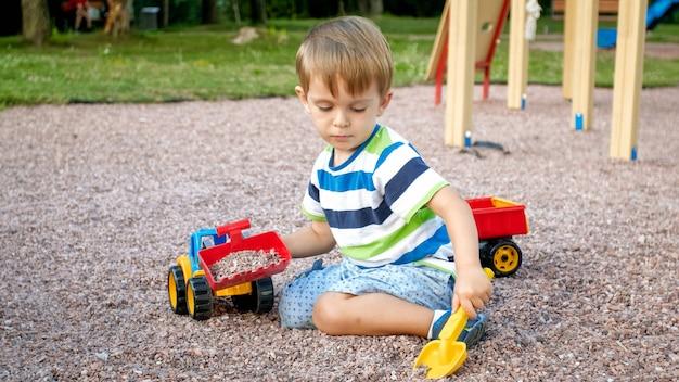 おもちゃのプラスチック トラックや掘削機で遊び場で砂を掘る幸せな笑顔の 3 歳の子供男の子のクローズ アップの肖像画