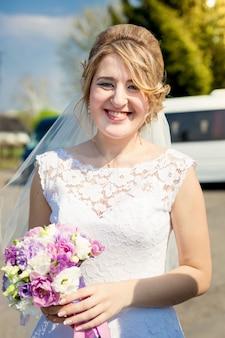 Портрет крупным планом счастливой улыбающейся невесты, позирующей в парке со свадебным букетом