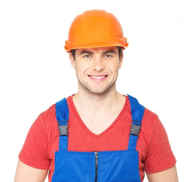 白い背景で隔離の制服を着た幸せな労働者のクローズアップの肖像画