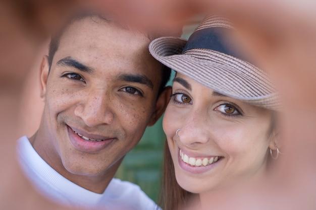 幸せな若い多民族のカップルのクローズアップの肖像画笑顔と炉床のため息を一緒に-愛と友情異人種間の人々-関係の男の子と女の子