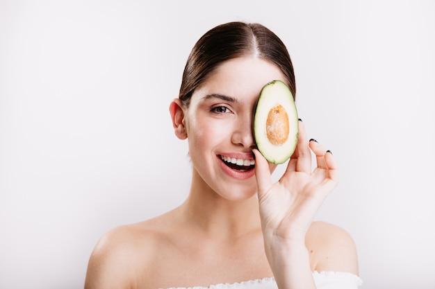 Портрет крупного плана здоровой девушки с чистой сияющей кожей, позирующей с авокадо на белой стене.