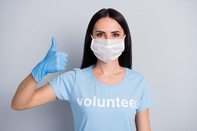 彼女のクローズアップの肖像画彼女の素敵な魅力的なコンテンツ女の子medicdoc自発的に灰色のパステルカラーの背景の上に分離されたサムアップ広告アドバイス療法を示しています