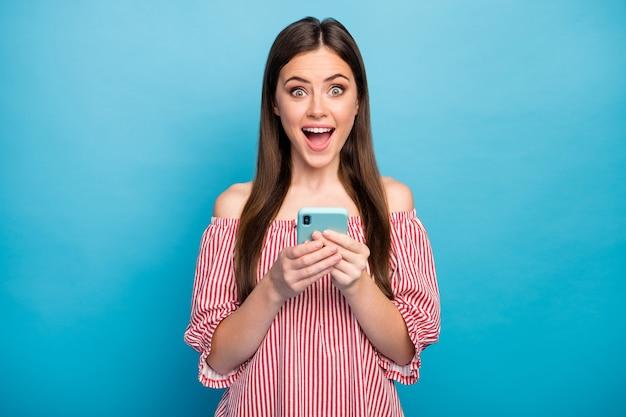 彼女のクローズアップの肖像画彼女は明るい鮮やかな輝きの鮮やかな青い色の背景の上に分離されたガジェットの新しいメディアアプリ5gを使用して素敵な魅力的な素敵な陽気な陽気な茶色の髪の少女