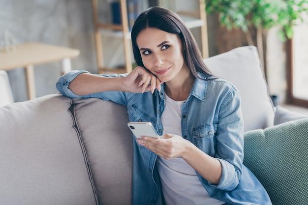 Портрет крупным планом, она красивая привлекательная милая жизнерадостная задумчивая задумчивая девушка-брюнетка, сидящая на диване с помощью устройства, просматривающего веб-социальную сеть в современной промышленной квартире на чердаке в помещении