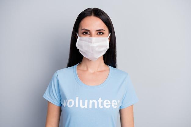 彼女のクローズアップの肖像画彼女は素敵な魅力的な素敵なコンテンツ女の子medicdoc自主的な労働者の仕事灰色のパステルカラーの背景の上に分離された保護マスクを身に着けています