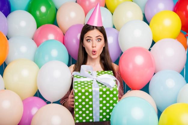 Портрет крупным планом, она милая, привлекательная, симпатичная, очаровательная, пораженная, веселая, веселая, длинноволосая, держит в руках подарочные надутые губы среди множества красочных воздушных шаров.