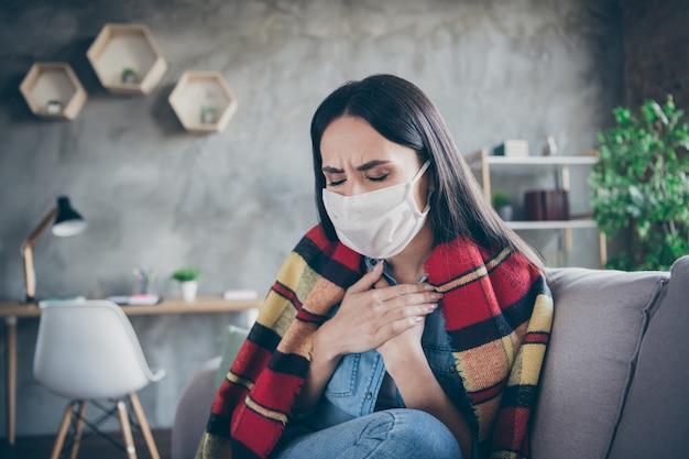 Портрет крупным планом, она красивая привлекательная больная депрессивная брюнетка, сидящая на диване, плохо себя чувствует, грипп, грипп, самоизоляция, терапия гриппа с высокой температурой в современной квартире промышленного дома на чердаке