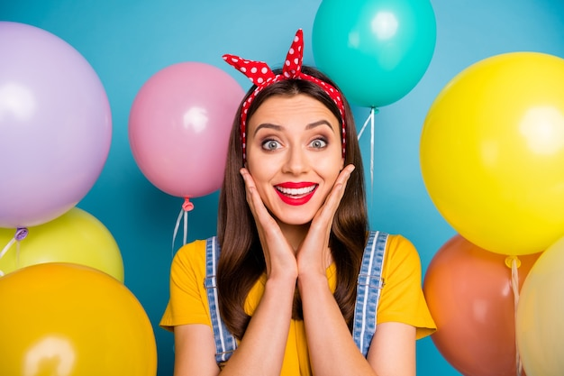 彼女のクローズアップの肖像画彼女の見栄えの良い魅力的な素敵なかわいい魅力的なかわいい陽気な陽気な嬉しい女の子は、明るい鮮やかな輝きの鮮やかな青い色の背景の上に分離された空気球の中で楽しんでいます