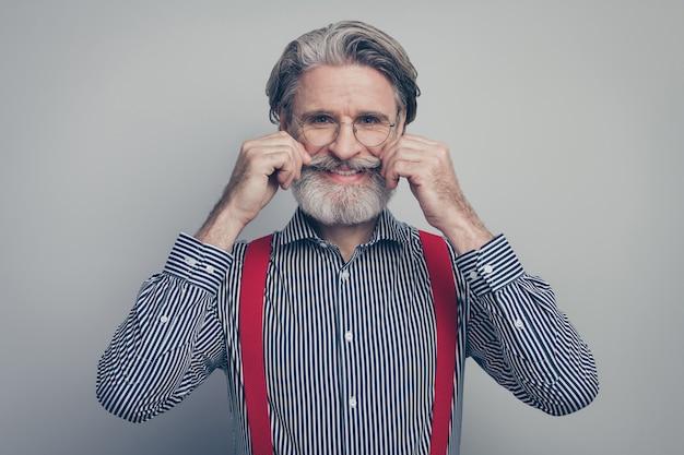 彼の素敵な魅力的なファッショナブルな手入れの行き届いた陽気な陽気な男のクローズアップの肖像画は、灰色のパステルカラーの背景の上に分離された口ひげ理髪店サービスに触れています