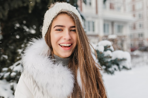 雪に覆われた通りで屋外ポーズニット帽子でうれしそうな笑顔の女性のポートレート、クローズアップ。庭で週末を過ごす冬の時間を楽しんでいる青い目をした陽気なブロンドの女性。