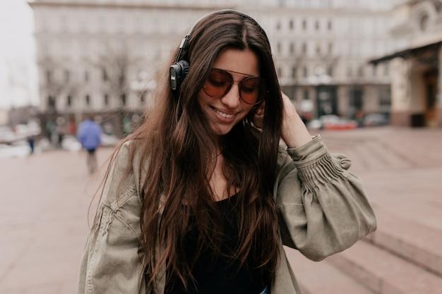 주말에 시간을 보내는 헤드폰에 웃는 여성 모델의 도시 야외 촬영에서 음악과 함께 편안한 즐거운 웃는 여자의 근접 촬영 초상화